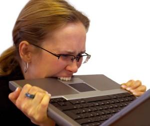 Frustated woman biting laptop